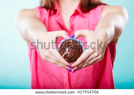 Hands making heart shape holding delicious tasty sweet chocolate muffin. Confectionery food love. - stock photo