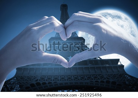 Hands making heart shape on the beach against large moon over eiffel tower - stock photo