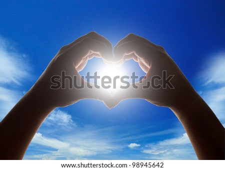 Hands making heart shape with sun in center and cloudy blue sky in background - stock photo