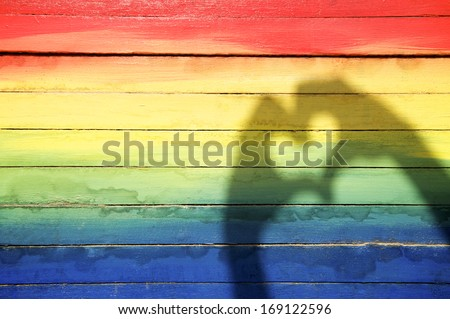 Hands making love heart shadow symbol of tolerance on gay pride rainbow colors painted on slats of weathered wood - stock photo