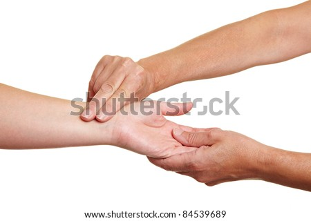 Hands measuring blood pressure with fingers at wrist - stock photo