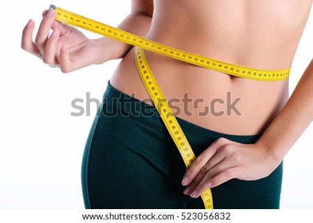 hands measuring waist with a tape. Fit and healthy woman on white background