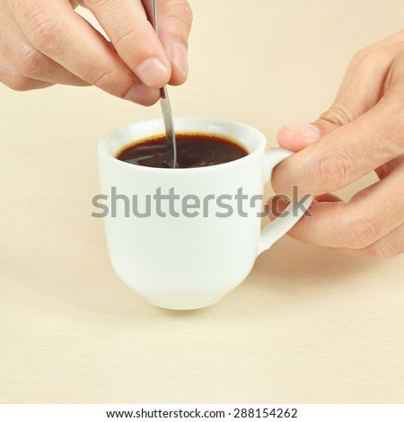Hands mixing with a spoon of black coffee in the cup - stock photo