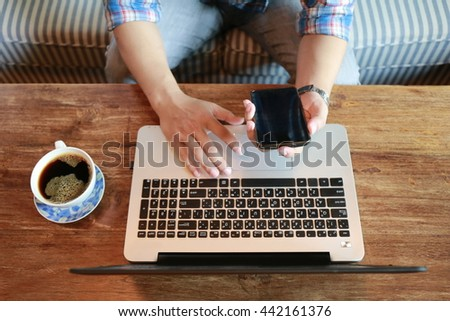 Hands multitasking man working on laptop connecting wifi internet, businessman hand busy using phone at office desk, finger typing on keyboard laptop computer sitting at wooden table,hardworking life