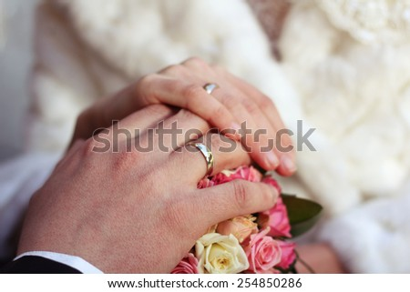 Hands newlyweds with rings. Wedding ceremony. Hands of the bride and groom at a wedding bouquet. Bouquet of roses and hands with rings. Marriage, wedding. - stock photo