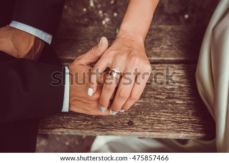 Hands newlyweds with wedding rings on background wooden texture