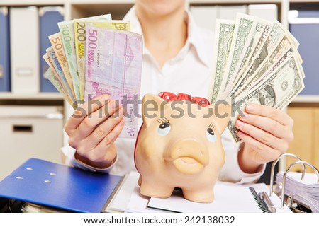 Hands of a business woman holding Dollar and Euro bills close to a piggy bank - stock photo