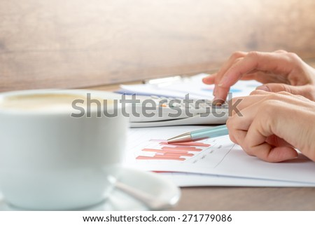 Hands of a businesswoman working on graphs analyzing the statistics using a desktop calculator, close up view.