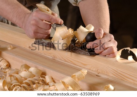 Hands of a carpenter planed wood, workplace - stock photo
