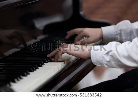 Hands of a child playing the piano closeup