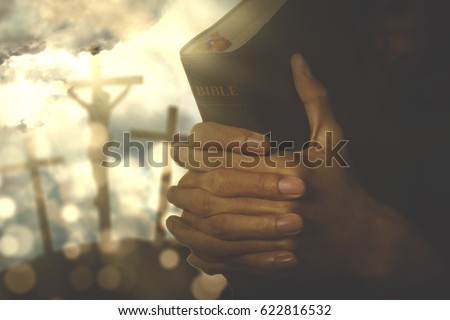Hands of a Christian man holding a bible while praying to God with three crucifixes under sunbeam