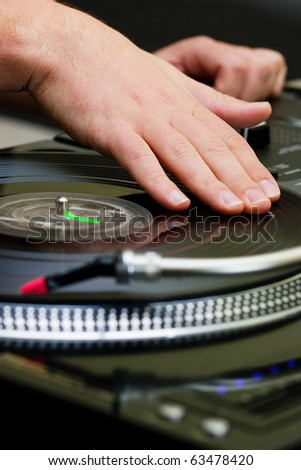 Hands of a disk jockey playin the record on the turntable