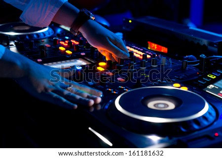 Hands of a DJ mixing music at a disco or concert with one hand on the switches and one held near the vinyl record on the turntable - stock photo