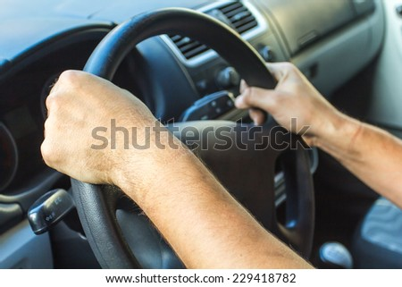 Hands of a driver on steering wheel of a car