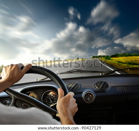 Hands of a driver on steering wheel of a car and empty asphalt road with motion blurred sky - stock photo