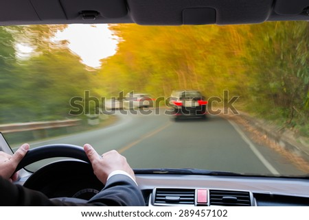 Hands of a driver on steering wheel of a car on highway - stock photo