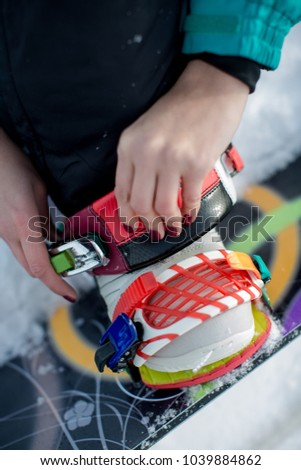 Hands of a girl locking colored snowboard bindings on white snow