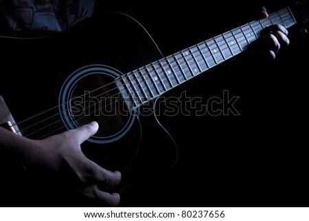 Hands of a guitarist playing guitar at night