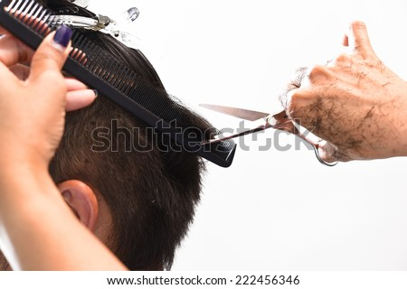 Hands of a hair stylist trimming hair with a comb and scissors - stock photo