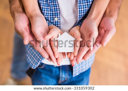 Hands of a happy young family holding little house, moving to a new home - stock photo