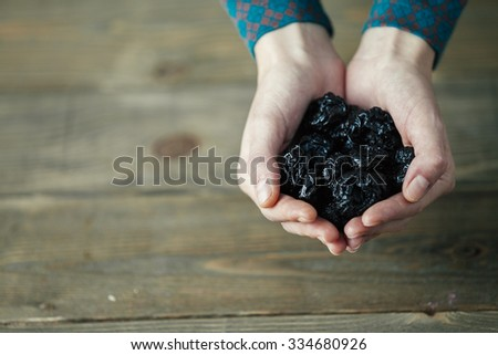 hands of a lady with full of dried plums on wooden background - stock photo