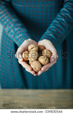 hands of a lady with full of walnuts - stock photo