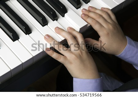 hands of a little boy on the piano keys close up