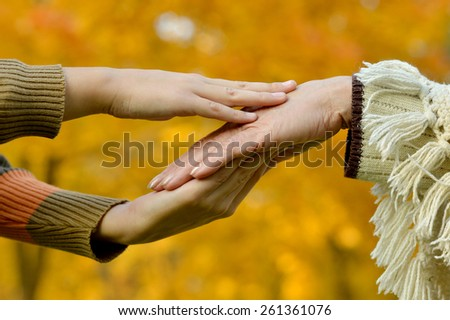 hands of a loving couple on a background of autumn leaves - stock photo