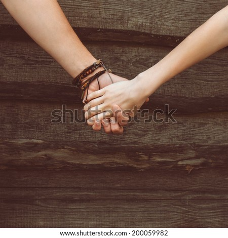 hands of a loving couple on a wooden background