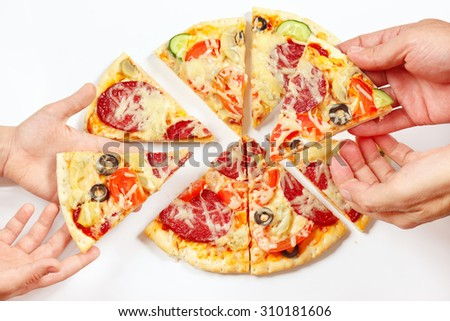Hands of a man and a child snapping up pieces of a tasty pizza  - stock photo