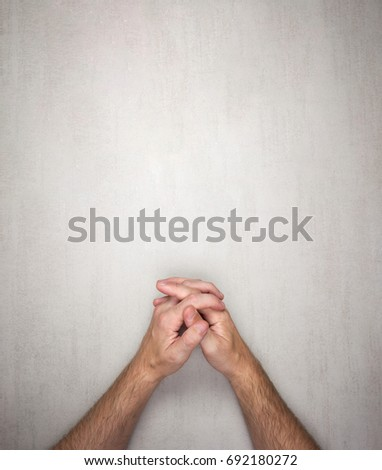 hands of a man are folded into a lock on a gray background, top view. mock up for text, phrases, lettering