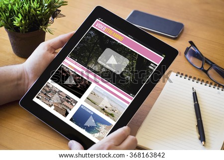 hands of a man holding a video streaming device over a wooden workspace table. All screen graphics are made up. - stock photo