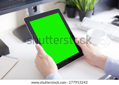 hands of a man holding blank tablet device over a workspace table - stock photo
