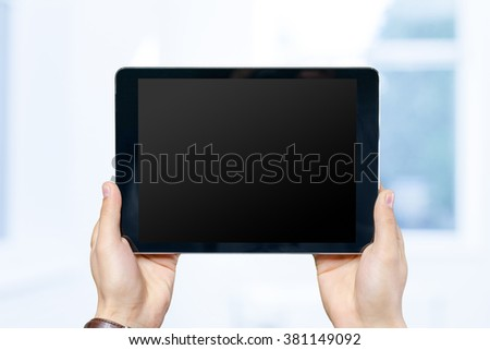Hands of a man holding digital tablet
