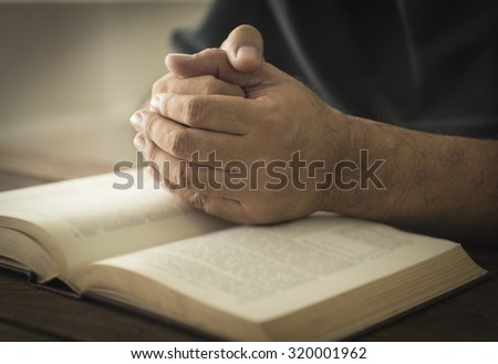 Hands of a man in prayer on a Holy Bible . religion concept - stock photo