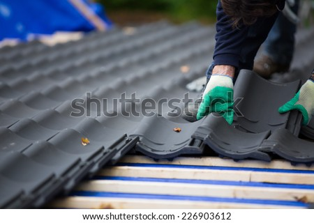 Hands of a man laying tiles on the roof while roofing a house near the city of Breda, Netherlands, Europe, in a traditional craftsman way - stock photo