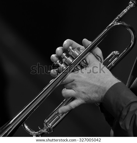 Hands of a man playing a trumpet in black and white - stock photo