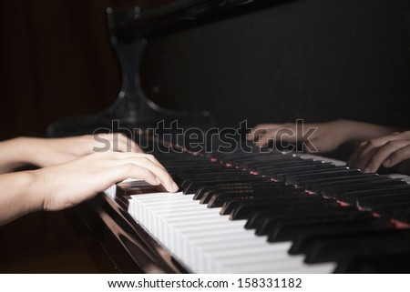 Hands of a man playing piano - stock photo
