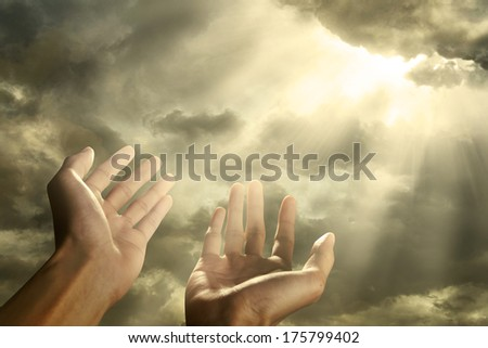 Hands of a man reaching to towards sky - stock photo