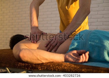 hands of a masseuse during massage back - stock photo