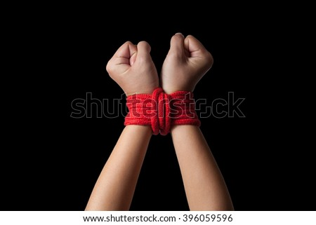 Hands of a missing kidnapped, abused, hostage, victim woman tied up with rope in emotional stress and pain, afraid, restricted, trapped, call for help, struggle, terrified. - stock photo
