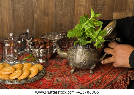 Hands of a muslim woman preparing mint tea the traditional way - stock photo