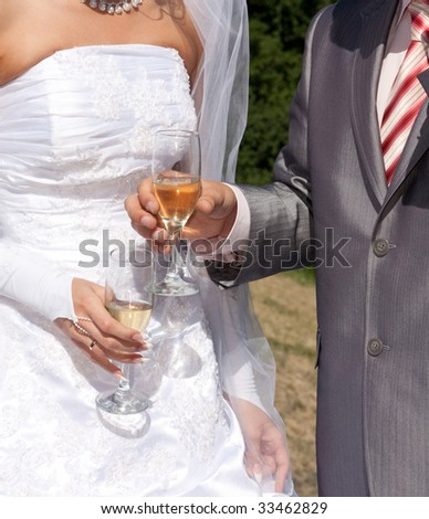 Hands of a newly-married couple with glasses
