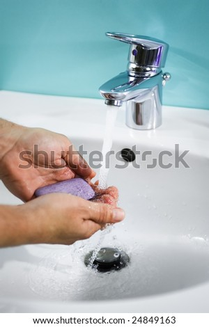 Hands of a person being washed under a tap. Hygiene is important. - stock photo