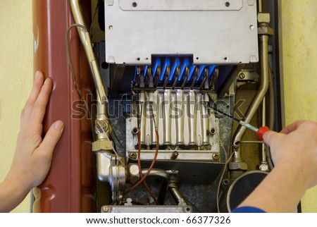 hands of a plumber repairing a gas heating - stock photo