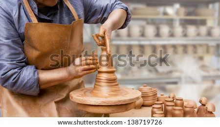 hands of a potter, creating an earthen jar on the circle. Potter's wheel. Horizontal - stock photo
