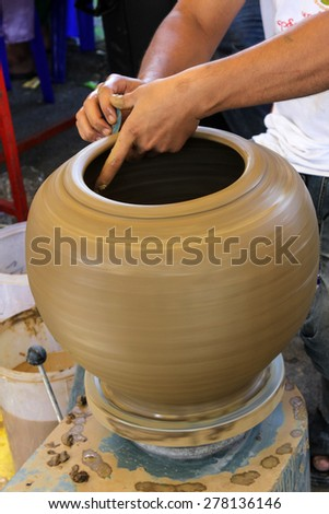 Hands of a potter making in clay on pottery wheel - stock photo
