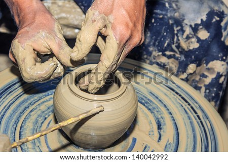 Hands of a potter with creating an earthen jar on the circle