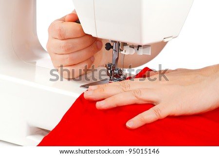 Hands of a seamstress at the sewing machine on a white background - stock photo