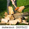 Hands of a strong man splitting wood with an axe, focus is on the axe, motion freezing in the moment it split - stock photo